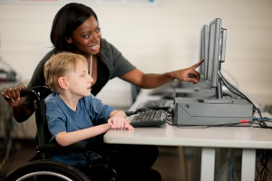 A boy in a wheelchair at the computer.